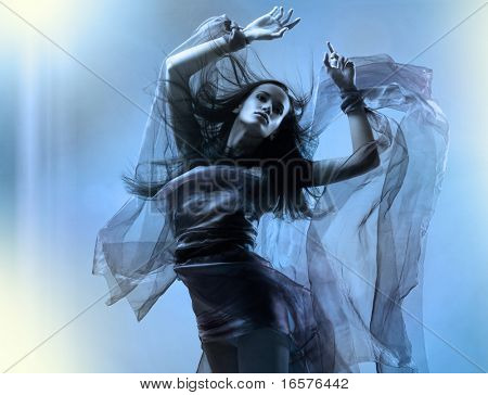 Portrait of a dancing sexy young woman with flying hair and fabric