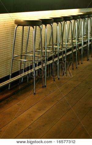 Empty row of stools at a bar