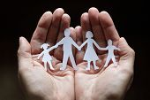 stock photo of figurine  - Cutout paper chain family with the protection of cupped hands - JPG