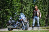 Постер, плакат: Biker Standing By His Custom Made Cruiser Motorcycle
