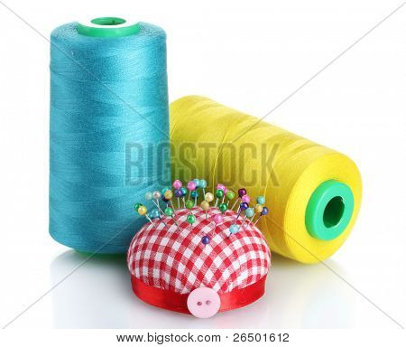Bobbins of thread with  pinheads in pin-cushion isolated on white