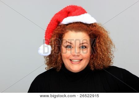 Beautiful young woman wearing a Santa hat over neutral background