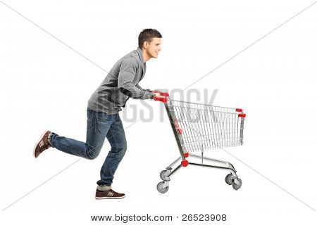 Young man running and pushing an empty shopping cart isolated on white background