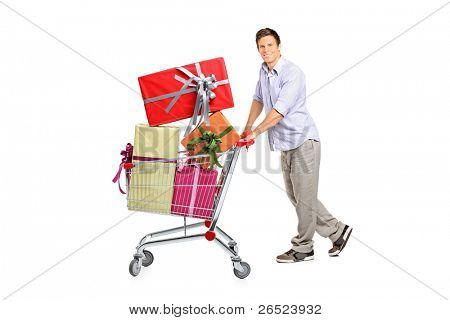 Young man pushing a shopping cart full with gifts isolated against white background