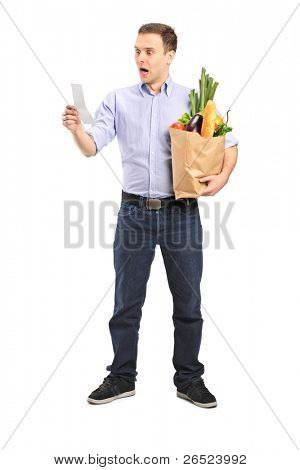 Full length portrait of a surprised man looking at store receipt and holding a paper bag isolated on white background