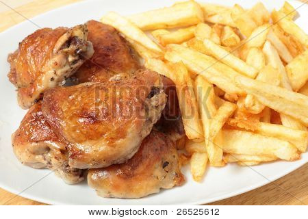 A serving dish piled with roast lemon chicken thighs and French fries, or chips