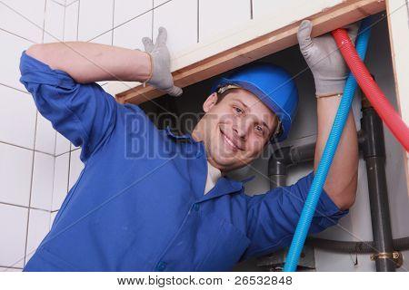 Man fixing plumbing in bathroom