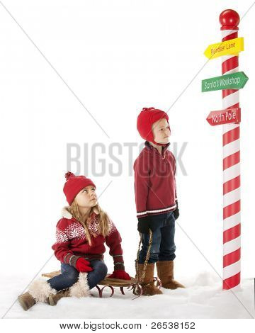 Having walked with a sled to see Santa, they stop at a colorful sign post get determine the direction.  On a white background with plenty of space for your text.