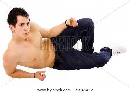 Young sensual man lying on the floor, studio shot
