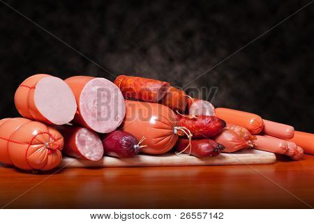A variety of processed cold meat products, on a wooden cutting board.