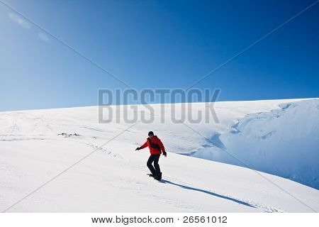 Man moves on snowboard. Glacier in background. Antarctica