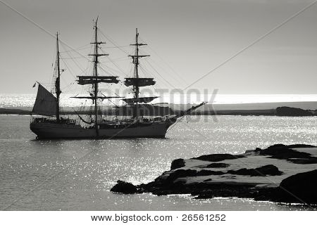 Sailing ship at dawn among the icebergs in Antarctica