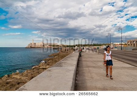 HAVANA - NOV 16: A young girl walks along El Malecon on November 16, 2010 in Havana. El Malecon attracts tourists and locals alike for its scenic views.