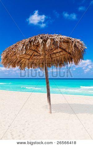 A straw umbrella on a beautiful tropical beach