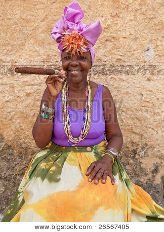 HAVANA-MARCH 28:Woman with typical clothes and a huge cuban cigar on March 28,2011 in Havana.People dress in a way that represents the cuban nationality can still be found in the streets of Old Havana