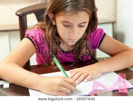 Small girl working on her school project at home