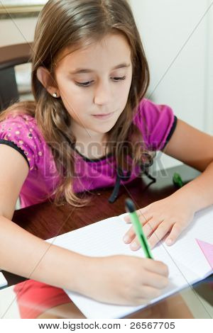 Beautiful small girl working on her school project at home