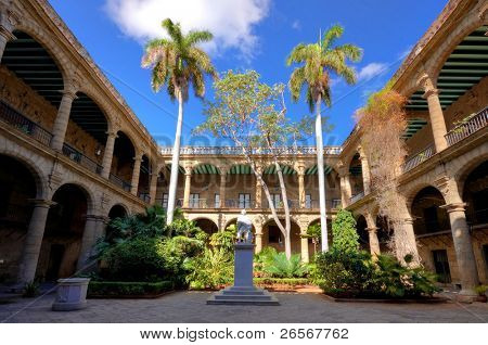 The ancient spanish government palace in Old Havana with a statue of Christopher Columbus and exuberant tropical vegetation