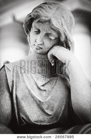 Statue of a beautiful young woman with a sorrow expression processed with a dreamy look in black and white