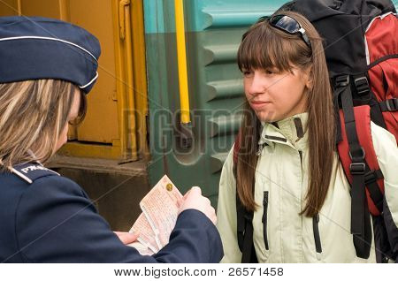 The woman expects embarkation to a train with a red backpack