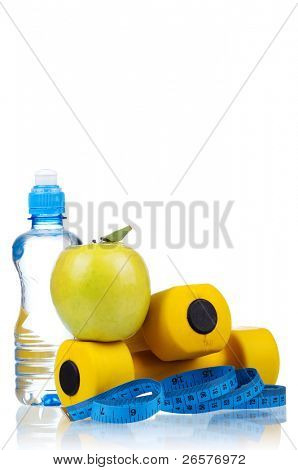 Yellow one kilogram dumbbells with apple, bottled water and measuring tape isolated on white background