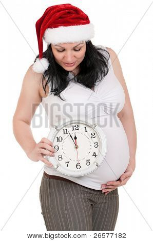 Portrait of a pregnant woman in santa hat with clock over white background. Third trimester.