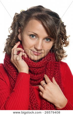 Portrait of a young woman in warm sweater and scarf with happy smile posing on white
