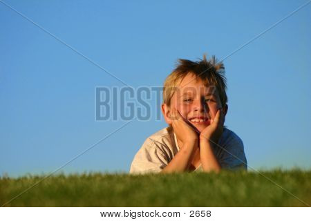 Boy Smiling In The Grass