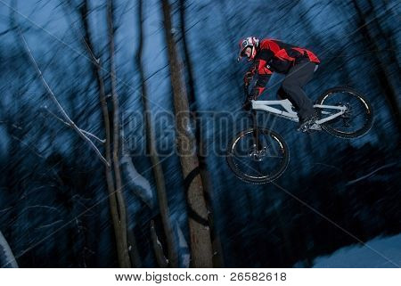 The young man jumps on a bicycle from a springboard
