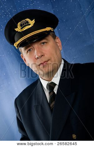 A pilot in uniform on blue background.