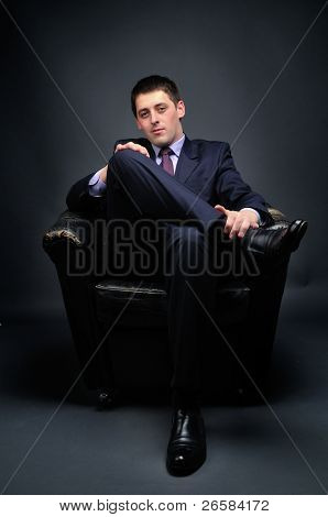 Young bussinessman sitting in black chair