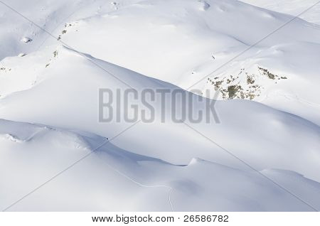Aerial View Of Snow Covered Mountains With Single Tracks