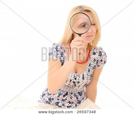 Attractive young blonde holding magnifying glass showing big eye
