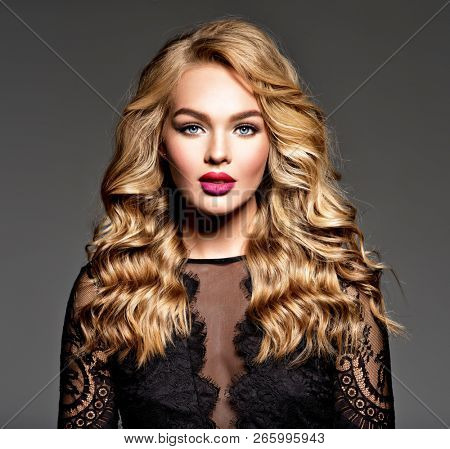 poster of Blond woman with long curly beautiful hair. Makeup. Fashion make-up. Fashionable girl dressed in bla
