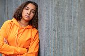Beautiful mixed race African American girl teenager female young woman outside wearing an orange hoo poster