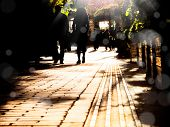 silhouetted  people walking on street and sunbeam poster