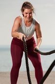 High Intensive Fitness Workout. Work Hard. Young Fit Woman Training With Battle Ropes On The Beach A poster