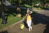Joyful Traveler Tourist Woman In Yellow Summer Casual Clothes With Suitcase Keeping Hand Near Hat, W poster
