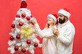 Happy Family Celebrate New Year And Christmas. Happy Couple Decorating Christmas Tree. Family Decora poster