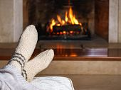 Feet In Woollen Socks And Knitted Plaid In Front Of The Fireplace. Close Up On Feet. Cozy Relaxed Ma poster