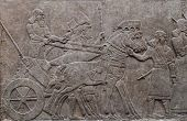 stock photo of chariot  - Relief of ancient assyrian warriors in a horse drawn chariot - JPG