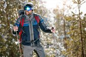 Extreme winter sports – Smiling man hiking in the forest poster