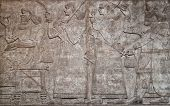 stock photo of babylon  - Ancient assyrian clay relief depicting a row of warriors with weapons and text written in cuneiform writing - JPG