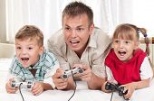 Happy family - father and children playing a video game