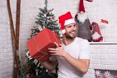 Man In Santa Hat Hold Christmas Present. Online Christmas Shopping. New Year Scene With Tree And Gif poster