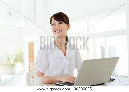 Beautiful business woman using a laptop computer. Portrait of asian.