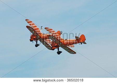 EASTBOURNE, ENGLAND - AUGUST 11: The Breitling Wingwalkers display team perform at the Airbourne airshow on August 11, 2012 at Eastbourne, East Sussex, England. The team fly 1940s Boeing Stearman biplanes.