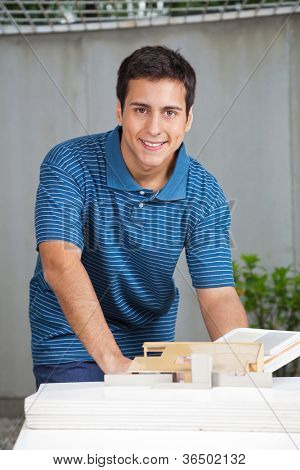 Portrait of young male architect in casual wear working on project