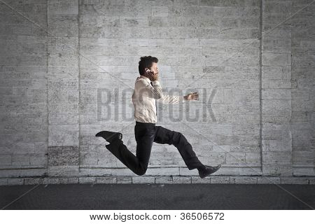 Young businessman running fast while talking on the mobile phone