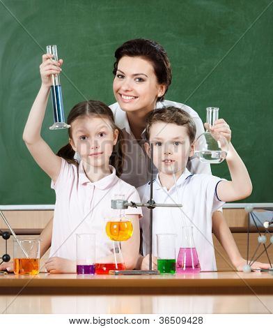 Little pupils study chemistry with their attractive school teacher
